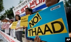 FILE - South Korean protesters hold signs during a rally to denounce deploying the Terminal High-Altitude Area Defense, or THAAD, in front of Defense Ministry in Seoul, South Korea, July 8, 2016.
