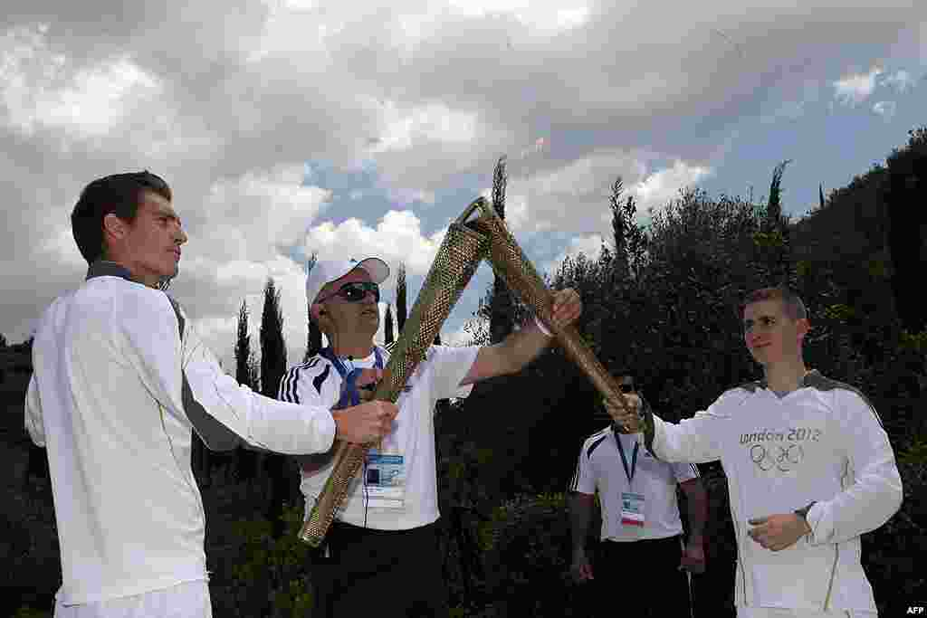 Second Olympic Torch bearer, Alex Loukos from Great Britain, right, receives the Olympic torch from Spyros Gianniotis, left. (AP)