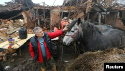 Farmer Tomislav Suknaic touches his horse in front of his damaged household in Majske Poljan village after an earthquake in Croatia, December 30, 2020. REUTERS/Antonio Bronic