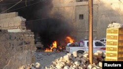 Mobil dilalap api dalam bentrokan di kota Ramadi (16/5).