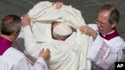 Le pape François se change à la fin d'une cérémonie de canonisation, 18 octobre 2015. (AP Photo/Alessandra Tarantino)
