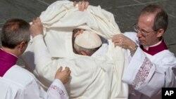 Le pape François aidé à se changer lors d'une cérémonie de canonisation à la place St Pierre, Vatican, 18 octobre 2015. (AP Photo/Alessandra Tarantino)