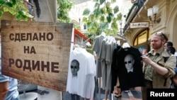 تیشرتهايی با تصاویر ولادیمیر پوتین، رئیس جمهوری روسیه، در معرض فروش در مرکز مسکو. علامتی که نصب شده میگويد: «ساخت وطن پدری» -- ۲۱ خرداد (۱۱ژوئن)