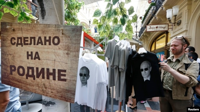 "FILE - T-shirts, displaying images of Russia's President Vladimir Putin, are on sale at GUM department store in central Moscow, June 11, 2014. The sign reads ""Made in Fatherland."""