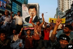 FILE - Bangladeshi opposition activists shout slogans carrying a portrait of Elias Ali, an opposition politician who is suspected to have been abducted by security forces in Dhaka, May 9, 2012.