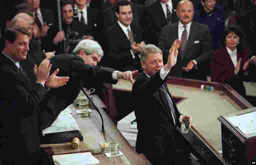 លោកប្រធានាធិបតី Bill Clinton ទទួលស្វាគមន៍អ្នកចូលរួម ខណៈពេលដែលលោកត្រៀមខ្លួនថ្លែងសុន្ទរកថាស្តីពីស្ថានភាពប្រទេសជាតិជាលើកទី២ នៅមុខសមាជិករដ្ឋសភាអាណត្តិទី១០៤ កាលពីថ្ងៃទី២៤ ខែមករា ឆ្នាំ១៩៩៥។ លោក Gore (ស្តាំ) អនុប្រធានាធិបតី និងលោក Newt Gingrich ប្រធានរដ្ឋសភា (កណ្តាល) សម្លឹងទៅមុខ។ (AP/Doug Mills)
