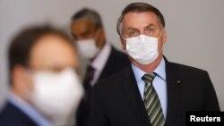 Le président brésilien Jair Bolsonaro avant une conférence de presse pour annoncer des mesures visant à freiner la propagation du coronavirus, Brasilia, 18 mars 2020. (REUTERS/Adriano Machado)