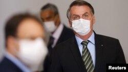 Le président brésilien Jair Bolsonaro portant un masque avant une conférence de presse pour annoncer des mesures judiciaires fédérales visant à freiner la propagation du coronavirus, Brasilia, 18 mars 2020. (Reuters/Adriano Machado)