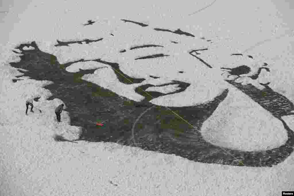 University students create an image of Marilyn Monroe by clearing snow off a soccer field, in Changchun, Jilin province, China.