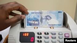 FILE - A cashier counts Qatari riyal notes at a money changer in Doha, May 28, 2013.