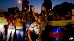 Manifestantes bloquean brevemente una calle en Plaza Altamira, municipio de Chacao, que el gobierno ha militarizado para suprimir las protestas antigubernamentales.