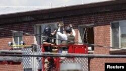Para petugas sedang melakukan langkah pengamanan untuk menjinakkan bom di apartemen tersangka penembakan, James Holmes di Aurora, Colorado (21/7).