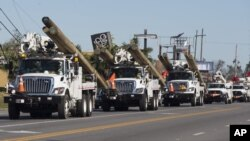 Camiones de la Compañía de Servicios Públicos de Oklahoma entregan postes y camiones en Florida, el 13 de Octubre de 2018.
