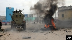 FILE - African Union Mission in Somalia (AMISOM) troops ride an armored vehicle past a burning car after it exploded in Somalia's capital, Mogadishu, Dec. 6, 2011.