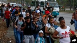 FILE - In this April 10, 2019 file photo, migrants walk at dawn as part of a new caravan of several hundred people sets off in hopes of reaching the distant United States, in San Pedro Sula, Honduras. (AP Photo/Delmer Martinez, File)