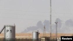 Après des opérations de déminage, la fumée s'élève au-dessus du site gazier dans le désert algérien.