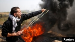 A Palestinian demonstrator hurls stones at Israeli troops during clashes at a protest demanding the right to return to their homeland, at the Israel-Gaza border east of Gaza City, April 6, 2018.