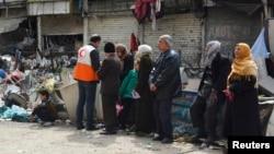 Người tị nạn chờ nhận lãnh phẩm vật cứu trợ tại trại tị nạn của người Palestine ở ngoại ô thủ đô Damascus ở Syria.