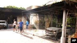 Des Libyens se promènent sur la cour intérieure du consulat américain à Benghazi le 12 septembre 2012
