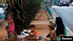 Homeless Syrian refugees rest by the side of a road in Beirut, July 22, 2013.