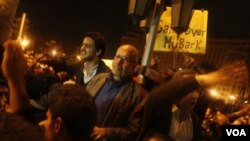 Mantan Ketua IAEA dan penerima Nobel perdamaian, Mohamed ElBaradei (tengah, berkacamata) bergabung dengan para demonstran di Lapangan Tahrir, Kairo, Minggu 30 Januari 2011.