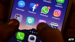 FILE - This photo taken March 22, 2018, shows apps for WhatsApp, Facebook, Instagram and other social networks on a smartphone.