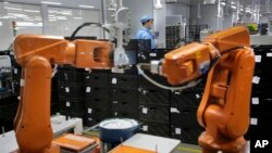 FILE - A Chinese worker is seen behind orange robot arms at work at Rapoo Technology factory in southern Chinese city of Shenzhen.