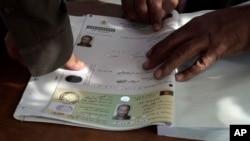 FILE - An Afghan man marks his application for voter registration with his fingerprint, Sept. 16, 2013.