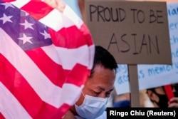 Seorang demonstran berdiri antara bendera AS dan sebuah poster saat unjuk rasa menentang kejahatan kebencian terhdapa warga Asia-Amerika di luar balai kota Los Angeles, California, Sabtu, 27 Maret 2021. (Foto: Ringo Chiu/Reuters)