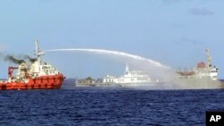 In this photo released by Vietnam Coast Guard, a Chinese ship, left, shoots water cannon at a Vietnamese vessel May 7, 2014. Vietnam tried to stop Beijing from setting up an oil rig in the South China Sea. (AP Photo/Vietnam Coast Guard)