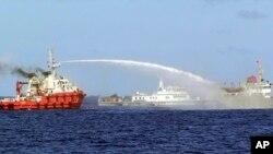 Một chiếc tàu của lực lượng tuần duyên Trung Quốc (trái) phun vòi rồng vào một tàu của Việt Nam hôm 7/5/2014, nhằm ngăn chặn tàu này tiến tới một giàn khoan dầu khổng lồ của Bắc Kinh ở nơi Hà Nội tuyên bố là thềm lục địa của mình.