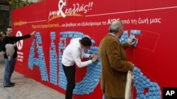 People take condoms from billboard on World Aids Day, Athens, Dec. 1, 2011.