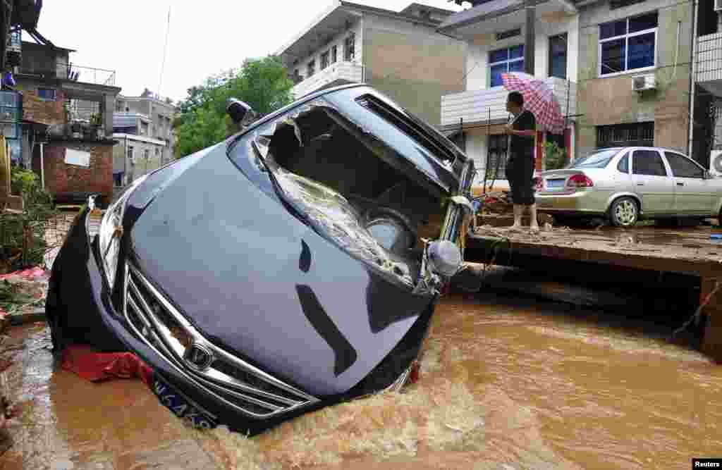 A car is stuck in a flooded river after a heavy rainfall in Dexing, Jiangxi province, China.