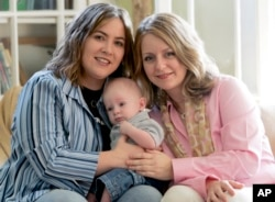 FILE - Cari Searcy, left, and Kim McKeand pose for a portrait with their son, Khaya, in Mobile, Ala., May 4, 2006.