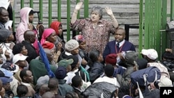 An immigration official addresses Zimbabweans as they queue in the rain outside immigration offices in downtown Johannesburg, as they attempt to become legal before what they fear will be a wave of deportations, 15 Dec 2010