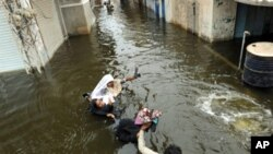 Pakistani men wade through floodwaters in Sujawal in southern Sindh province, Pakistan, 30 Aug 2010.