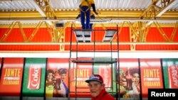 Seorang pekerja tengah membetulkan lampu di atas poster sponsor FIFA di luar stasiun kereta api di dekat stadion World Cup di Sao Paulo, Brazil (Foto: dok).
