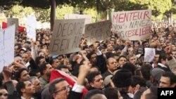 Người biểu tình giương biểu ngữ và hô khẩu hiệu trước trụ sở bộ nội vụ ở Tunis, đòi Tổng thống Zine El Abidine Ben Ali từ chức