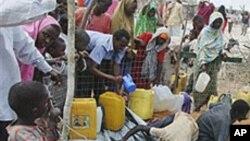Para pengungsi mengisi jirigen dengan air hujan di sebuah kamp di pinggiran Mogadishu, Somalia (foto: dok).