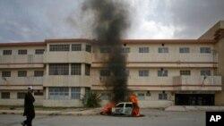 احتجاجیوں کی طرف سے نذر آتش کی جانے والی گاڑی سے شعلے اور دھواں بلند ہورہا ہے۔