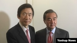 왕이(오른쪽) 중국 외교부장과 윤병세 한국 외교부 장관이 18일 독일 뮌헨 안전보장회의 현장에서 만나 인사하고 있다.