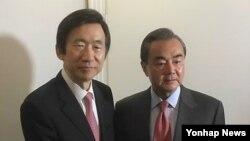 윤병세 한국 외교장관과 왕이 중국 외교부장이 18일 뮌헨에서 회담 전 악수하고 있다