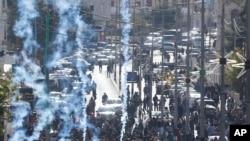 Pasukan Israel menembakkan gas air mata ke arah warga Palestina saat sebuah aksi unjuk rasa menentang keputusan Presiden AS Donald Trump yang mengakui Yerusalem sebagai ibu kota Israel di kota Bethlehem, Tepi Barat, 7 Desember 2017.