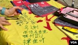 香港市民陳小姐五一勞動節在社民連街站留言支持在囚抗爭者及民主派人士。 (美國之音湯惠芸拍攝)