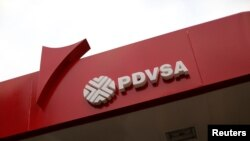 FILE - The corporate logo of the state oil company PDVSA is seen at a gas station in Caracas, Venezuela, March 22, 2017.