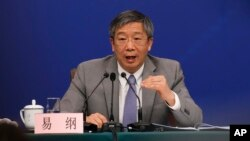 FILE - China's Central Bank Governor Yi Gang gestures as he speaks during a press conference on the sideline of the National People's Congress at the media center in Beijing, March 10, 2019.