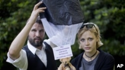 Tomas Mazetti and Hannah Frey with a human-rights message bearing teddy similar to ones they dropped in Belarusian airspace, Germany, Aug. 1, 2012.