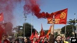 Một công nhân Italia thuộc công đoàn công nhân ngành kim loại giơ cao chiếc pháo hiệu trong cuộc đình công trong 8 tiếng đồng hồ ở Rome hôm 9/3/12