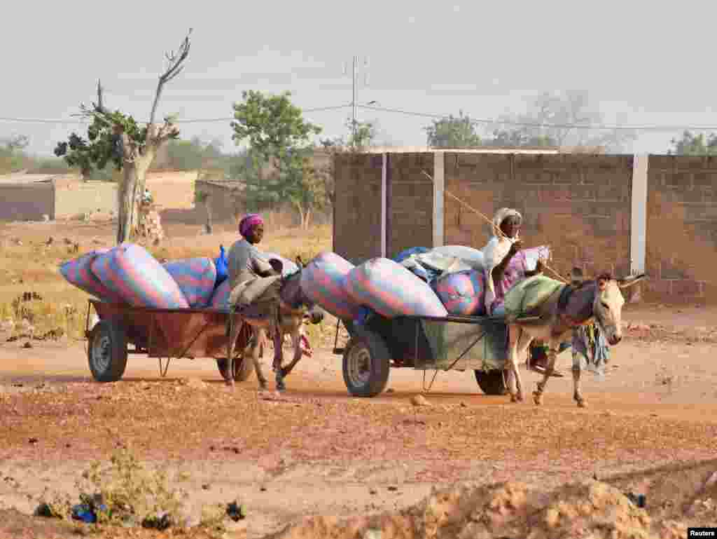 Displaced women, who fled from attacks of armed militants in town of Roffenega, ride donkey carts loaded with food aid at the city of Pissila, Burkina Faso.