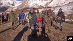 Tentara Nepal mengangkut korban salju longsor di kawasan Himalaya, Rabu (15/10).